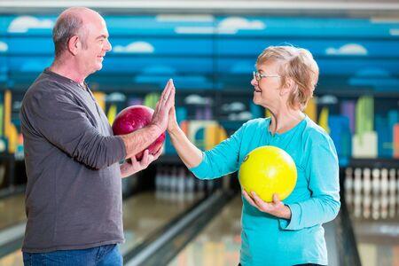 Lächelndes reifes Paar, das eine Bowlingkugel hält, die High-Five gibt