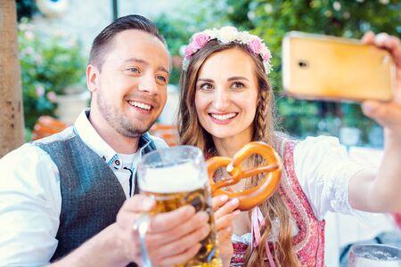 Fröhliches Paar im deutschen Biergarten macht ein Selfie-Foto mit dem Telefon