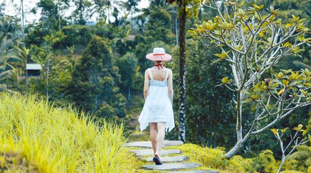 Woman in tropical vacation walking through the jungle holding her sunhat