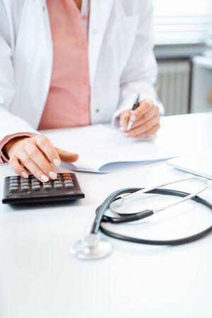 Close-up van arts die rekenmachine gebruikt die rekeningen schrijft en boekhouding doet