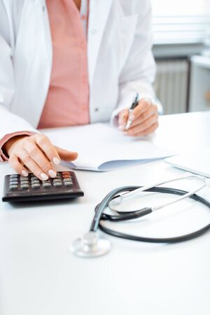 Closeup of doctor using calculator writing bills and doing bookkeeping