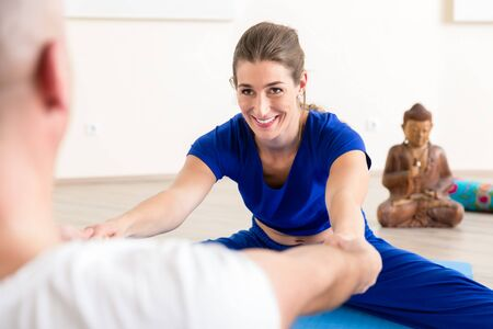 Smiling young woman performing stretching exercise with male instructor