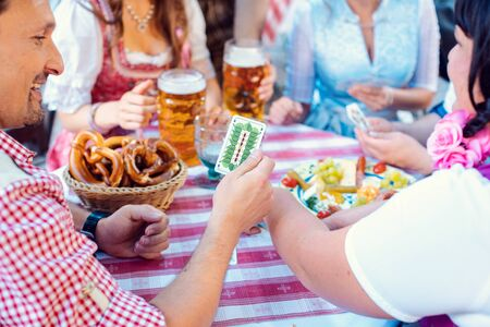 Friends in Bavarian beer garden playing traditional card game of Schafkopf