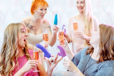 Best friends having fun during an adult toy party drinking sparkling wine
