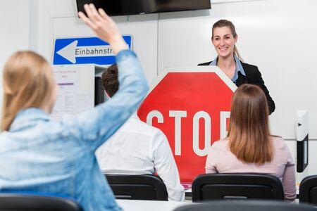 Teacher with class giving driving lessons explain traffic signs