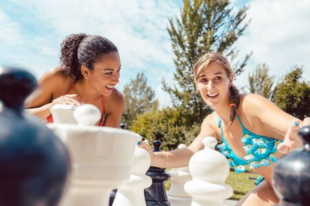 Two smiling women playing big chess in park