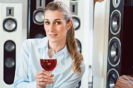 Femme ayant un verre de vin devant des haut-parleurs Hi-Fi appréciant la boisson et la musique Banque d'images