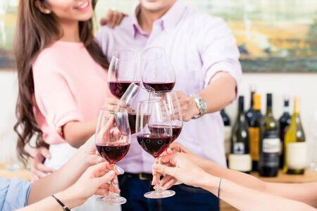 Close-up of loving couple toasting red wineglasses with friends