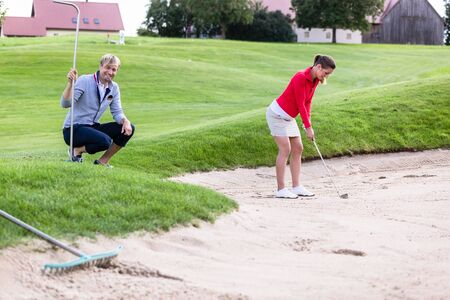 Smiling boyfriend looking at female golfer preparing for chipping the ball out of the bunker