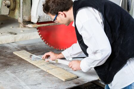Handyman in stone carving factory working at diamond saw