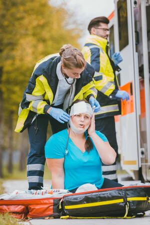 Emergency medics dressing head wound of injured woman after accident