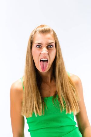 An angry young woman showing her tongue standing against white background