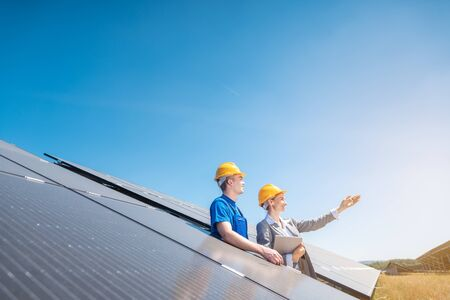 Worker and manager of solar farm looking into the sun standing amid photovoltaic panels