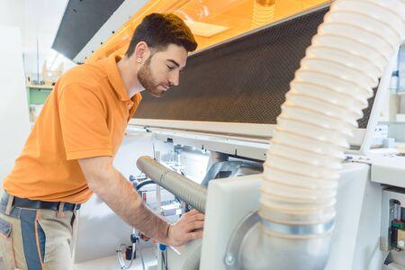 Carpenter adjusting veneer machine in his workshop Stockfoto