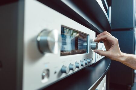 Hand einer Frau, die die Lautstärke des Hi-Fi-Verstärkers in ihrem Haus aufdreht