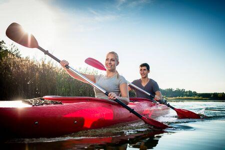 Heureux jeune couple pagayer en kayak au soleil