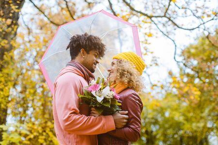 Man and woman of different ethnicity hugging in fall during a walk