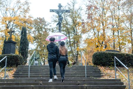 Man and woman walking up steps on cemetery towards a cross in autumn
