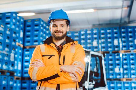 Werknemer in een expeditiebedrijf met zijn vorkheftruck in de camera kijken Stockfoto
