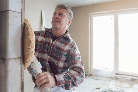 Plasterer man smoothing interior wall of new homes with machine