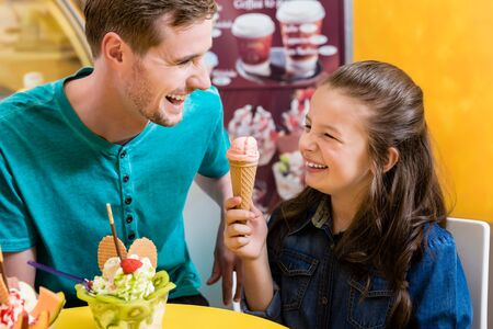 Dad and daughter eating ice cream with lots of fun Zdjęcie Seryjne