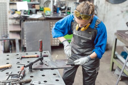 Woman mechanic working in metal workshop using clamps, screws, and spanner