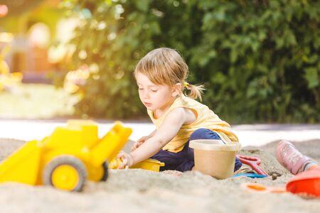 Kleines Mädchen, das viel Spaß mit ihren Spielsachen hat, die draußen im Sandkasten spielen