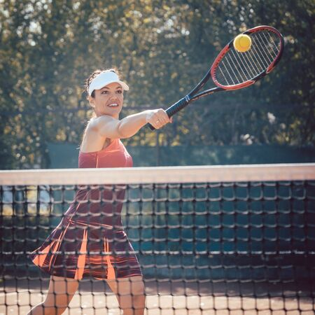 Woman in red sport dress playing tennis hitting the ball