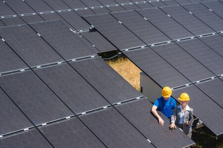 Two people standing amid solar cells in a power plant inspecting the modules Stok Fotoğraf