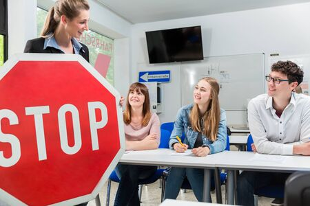Driving instructor holding theoretical part of driving lessons with stop sign in her hand