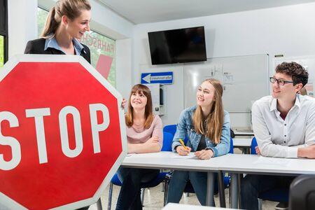 Instructeur de conduite tenant une partie théorique des cours de conduite avec un panneau d'arrêt à la main Banque d'images