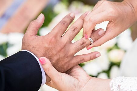 Bride putting ring on groom finger at Asian wedding