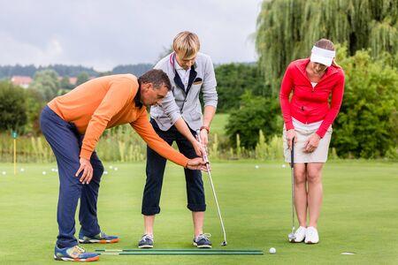 Istruttore di golf maschio maturo che insegna alla coppia a giocare a golf sul campo da golf Archivio Fotografico