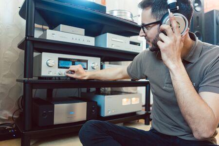 Mann dreht die Lautstärke der Hi-Fi-Heimstereoanlage für lautere Musik auf