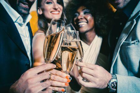 Männer und Frauen feiern Geburtstags- oder Neujahrsparty, während sie Gläser mit Sekt anstoßen