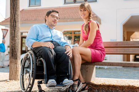 Man in wheelchair and woman eating nibbles spending time on a bench in summer