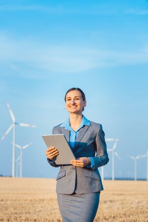 Investor in wind turbines with computer evaluating her investment on site looking pleased 版權商用圖片