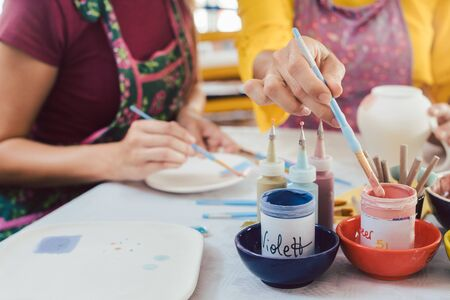 Woman coloring handmade dishes using brush to paint color