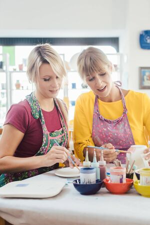Two girl friends painting their own handmade ceramics in a hobby workshop Banco de Imagens