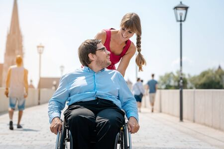 Woman and disabled man having a walk in their leisure time