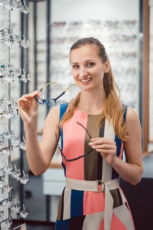 Woman shopping eyeglasses in optometrist store choosing between the models Stok Fotoğraf