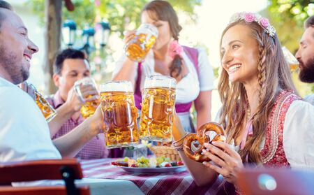 Couple looking at each other clinking glasses with huge amounts of beer in Bavarian pub