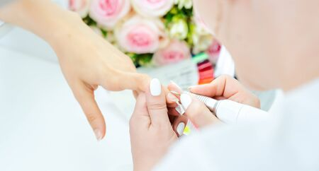 Hands of a skilled manicurist working on fingernails of a young woman Stock fotó