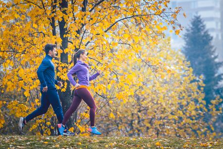 Woman and man jogging or running in park during autumn on a hill Фото со стока
