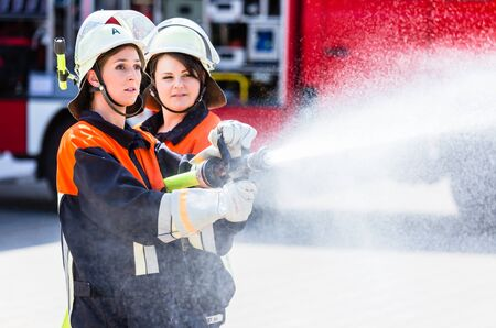 Female fire fighters spouting water to extinguish fire