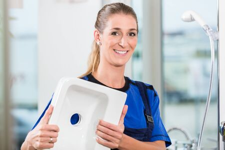 Portrait of a happy female worker looking at camera with professional confidence during work in a modern sanitary ware shop with high-quality ceramic fixtures Archivio Fotografico - 129243195