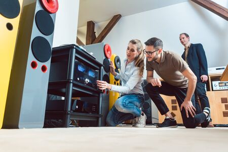 Young couple, woman and man, buying high-end stereo equipment in store