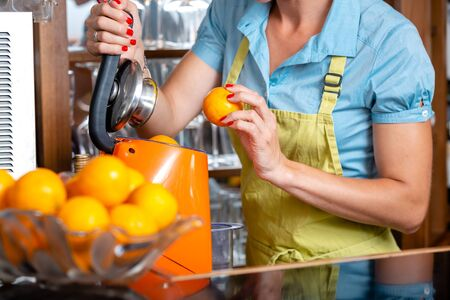 Close-up of a woman putting oranges in blender