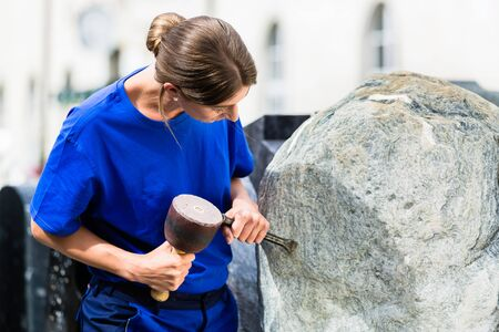 Female stonemason working on boulder with sledgehammer and iron
