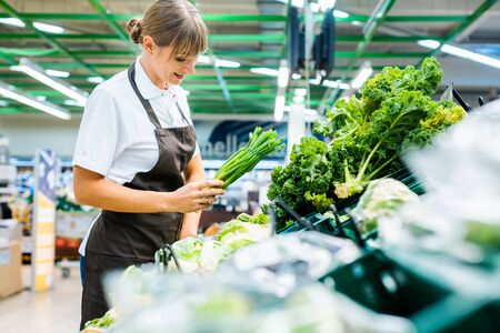 Shop assistant in supermarket re-stocking fresh vegetables into boxes Stock fotó